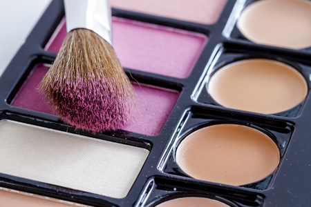 Close up of large cosmetic brush with pink blush dust sitting on palette of blush and skin cover up colors Stock Photo