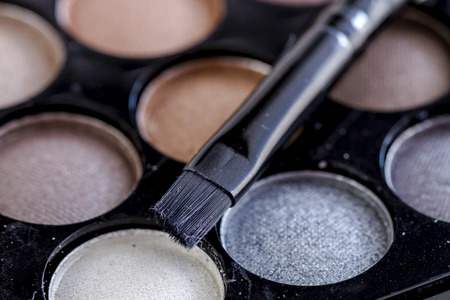 nudes: Close up of cosmetic brush sitting on top of palette of nude and gray eye shadow shades Stock Photo