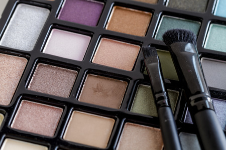 Two cosmetic brushes sitting on bright colorful palette of shimmering eye shadow colors