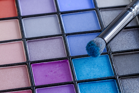 Cosmetic brush with bright blue eye shadow dust sitting on top of palette of blues and purples eye shadow shades