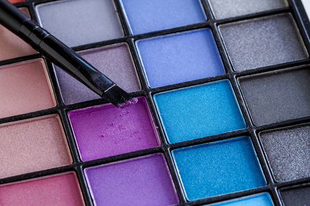Cosmetic brush with purple shimmering eye shadow dust sitting on top of palette of brightly colored eye shadow shades Stock Photo
