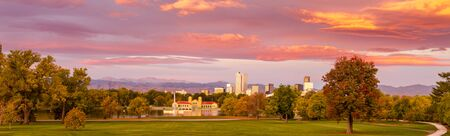denver skyline with mountains: Denver Colorado skyline from City Park with City Park Boathouse and Rocky Mountains in background on autumn morning