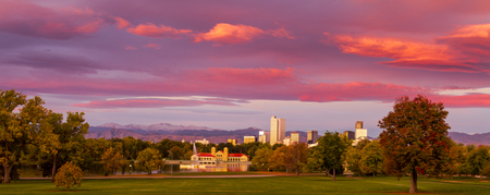 denver city skyline: Denver Colorado skyline from City Park with City Park Boathouse and Rocky Mountains in background on autumn morning