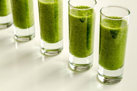shot glasses: Line of shot glasses filled with fresh spinach and kale detox health smoothie