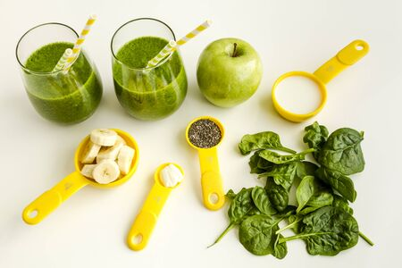 measuring spoons: Two glasses filled with spinach and kale green detox smoothie with yellow and green swirled straws surrounded by raw ingredients in yellow measuring cups and spoons