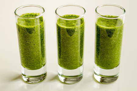 shot glasses: Three shot glasses filled with fresh spinach and kale detox health smoothie in a line