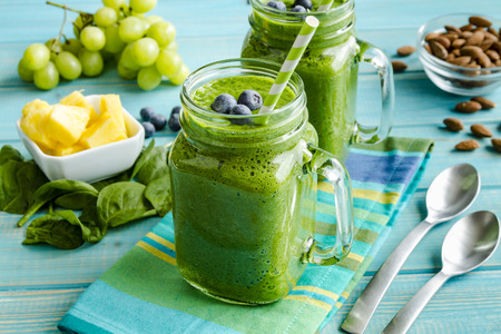 fruit juices: Mason jar mugs filled with green spinach and kale health smoothie with green swirled straw sitting with blue striped napkin and spoons