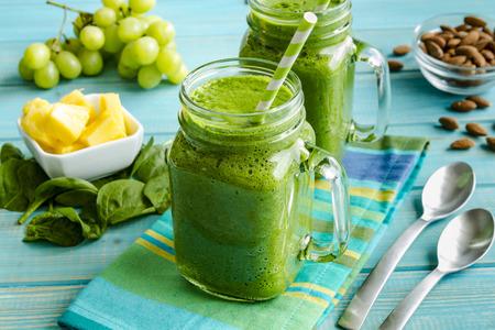 녹색 녹색 시금치와 케일 건강 스무디 가득 메이슨 항아리 잔은 블루 스트라이프 냅킨과 숟가락에 앉아 빨대를 소용돌이
