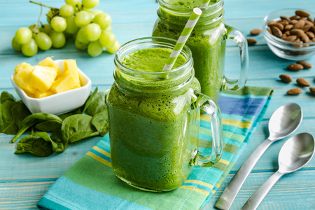 smoothie: Mason jar mugs filled with green spinach and kale health smoothie with green swirled straw sitting with blue striped napkin and spoons