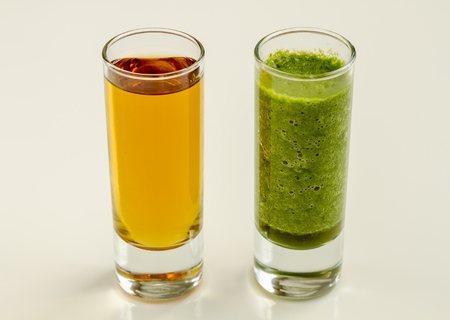 shot glasses: Good versus evil shot glasses filled with spinach and kale health detox smoothie and alcoholic beverage