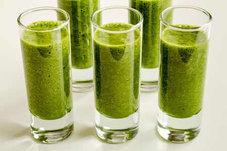 shot glasses: Group of shot glasses filled with fresh spinach and kale detox health smoothie in rows Stock Photo