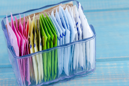 Packets of artificial sweeteners in glass container sitting on bright blue wooden table