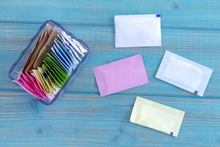 Pakete von künstlichen Süßstoffen in Glasbehälter mit einzelnen Pakete auf leuchtend blauen Holztisch sitzen Standard-Bild