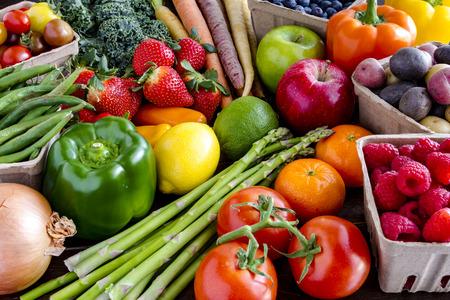 Verscheidenheid van verse rauwe biologische groenten en fruit in het licht bruine containers zitten op heldere blauwe houten achtergrond