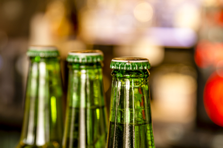 Three green bottles of beer in line sitting on bar with bar lights in background Banco de Imagens - 53921866