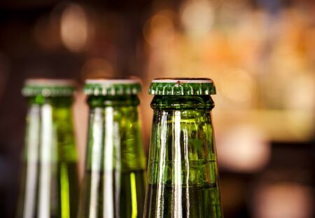 Three green bottles of beer in line sitting on bar with bar lights in background