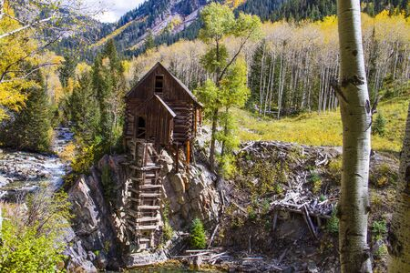 Fall colors surrounding abandoned historic landmark the Crystal Mill located on the Crystal River above the town of Marble Colorado on fall afternoon