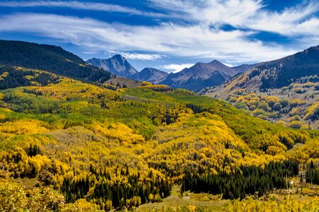wispy: Sunny autumn afternoon view of Capitol Peak near Aspen Colorado surrounded by valley filled with changing yellow Aspen trees and blue sky with wispy clouds