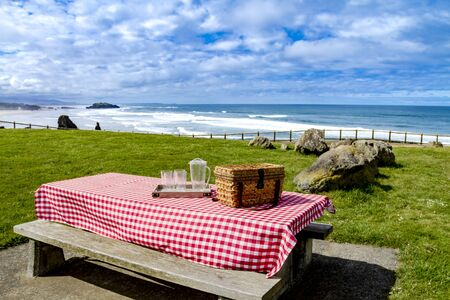 checkered tablecloth: Picnic along the coast overlooking the Pacific Ocean with picnic basket and red checkered tablecloth on wooden picnic table Stock Photo
