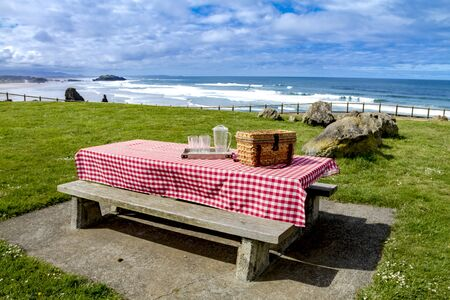 Picnic along the coast overlooking the Pacific Ocean with picnic basket and red checkered tablecloth on wooden picnic table