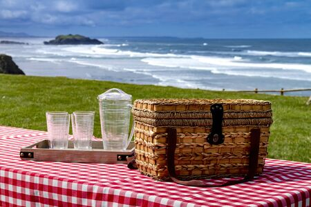 checkered tablecloth: Close up picnic along the coast overlooking the Pacific Ocean with picnic basket and red checkered tablecloth on wooden picnic table