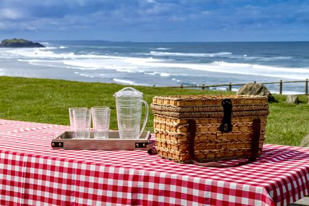 checkered tablecloth: Close up of picnic along the coast overlooking the Pacific Ocean with picnic basket and red checkered tablecloth on wooden picnic table Stock Photo