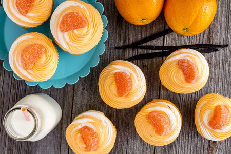 Orange and vanilla bean swirled cupcakes sitting on wooden table with bottles of milk, fresh oranges and whole vanilla beans