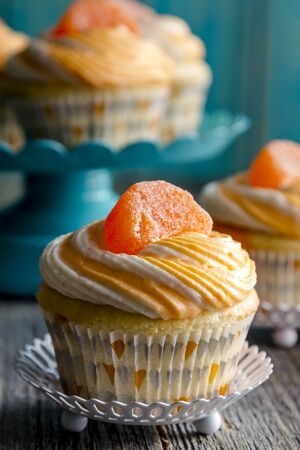 vanilla bean: Orange and vanilla bean swirled cupcakes on sitting on wooden table with teal blue wooden background Stock Photo