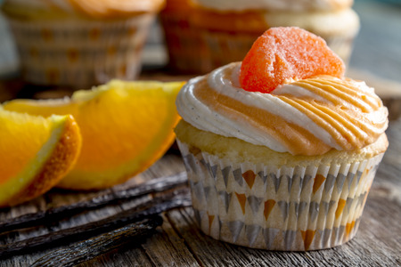vanilla bean: Close up of orange and vanilla bean swirled cupcakes with candy garnish sitting on wooden table with fresh orange slices and vanilla bean pods