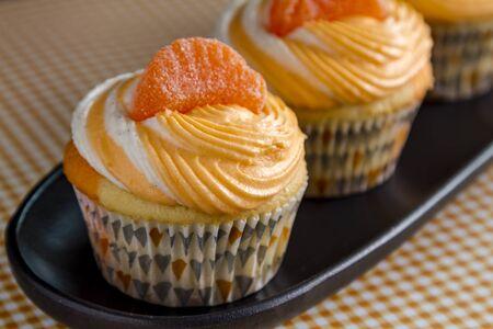 swirled: Row of orange and vanilla bean swirled cupcakes on black tray plate sitting orange gingham checkered background