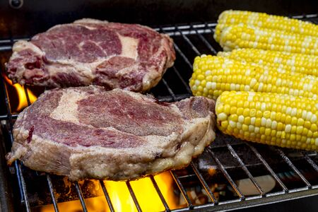barbequing: Close up of raw ribeye steaks and corn on the cob cooking over flames on grill