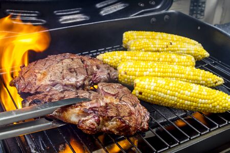 barbequing: Two ribeye steaks and corn on the cob surrounded by flames on grill with tongs flipping one steak over