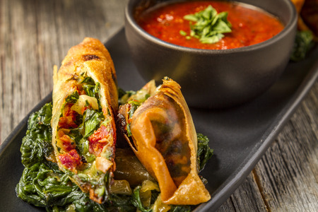 marinara sauce: Close up pf Tuscan spring rolls with sundried tomatoes, spinach, red onions, fontina cheese in wonton wrappers with bowl of marinara sauce sitting on black plate
