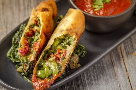 wrappers: Tuscan spring rolls with sundried tomatoes, spinach, red onions, fontina cheese in wonton wrappers with bowl of marinara sauce sitting on black plate Stock Photo
