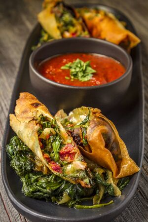 marinara sauce: Tuscan spring rolls with sundried tomatoes, spinach, red onions, fontina cheese in wonton wrappers with bowl of marinara sauce sitting on black plate Stock Photo