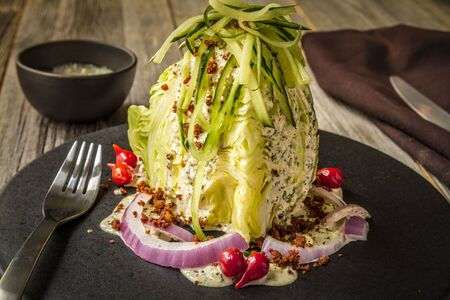 Classic iceberg wedge salad with bacon and blue cheese dressing with red onion and zucchini shreds on top sitting on black plate Banco de Imagens