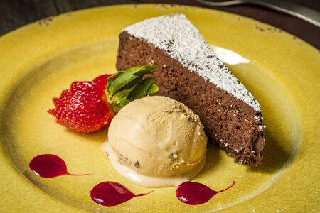 flourless chocolate cake: Slice of flourless chocolate cake dessert with salted caramel ice cream siiting on yellow plate with strawberry slices and sauce