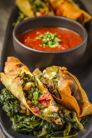 wrappers: Close up of Tuscan spring rolls with sundried tomatoes, spinach, red onions, fontina cheese in wonton wrappers with bowl of marinara sauce sitting on black plate