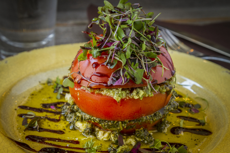 ricotta cheese: Fresh tomato tower filled with olive tapenade sitting on ricotta cheese, balsamic vinegar and olive oil and garnished with microgreens sitting on rustic yellow plate