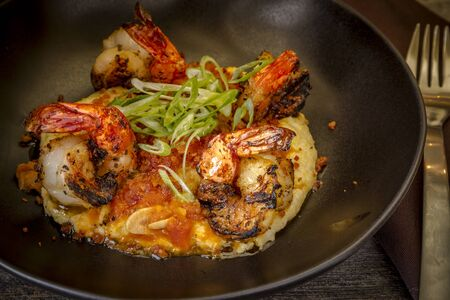 grits: Fresh grilled shrimp sitting on bed of creamy yellow grits with pancetta garnished with scallions in rustic black bowl Stock Photo