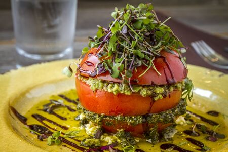 ricotta cheese: Close up of fresh tomato tower appetizer filled with olive tapenade sitting on ricotta cheese, balsamic vinegar and olive oil and garnished with microgreens sitting on rustic yellow plate Stock Photo