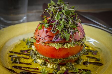 ricotta cheese: Fresh tomato tower appetizer filled with olive tapenade sitting on ricotta cheese, balsamic vinegar and olive oil and garnished with microgreens sitting on rustic yellow plate Stock Photo