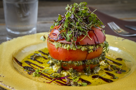 balsamic vinegar: Fresh tomato tower appetizer filled with olive tapenade sitting on ricotta cheese, balsamic vinegar and olive oil and garnished with microgreens sitting on rustic yellow plate Stock Photo