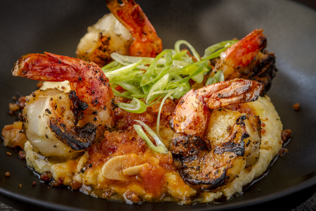 scallions: Close up of fresh grilled shrimp sitting on bed of creamy yellow grits with pancetta garnished with scallions in rustic black bowl Stock Photo