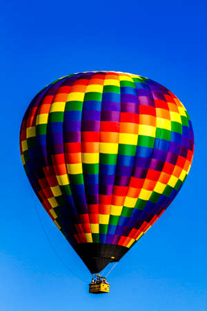 weightless: Brightly colored hot air balloon aloft in early morning blue sky