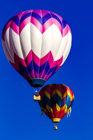 buoyant: Several brightly colored hot air balloons aloft in early morning blue sky