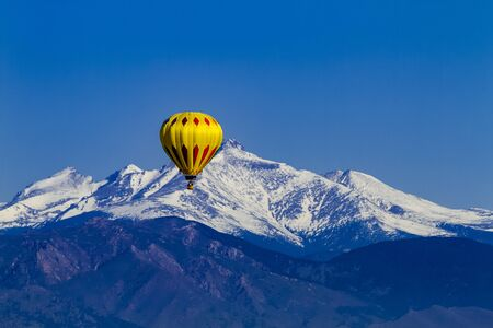 buoyant: Bright yellow hot air balloon aloft in early morning blue sky over snow covered mountains in the distance