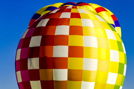 buoyant: Brightly colored hot air balloons against blue morning sky