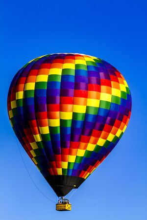 buoyant: Brightly colored hot air balloon aloft in early morning blue sky