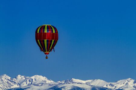 buoyant: Brightly colored hot air balloon aloft in early morning blue sky over snow covered mountains in the distance
